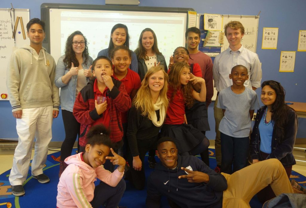 Georgetown student tutors and DC Public School students with the DC STEM program gather together in the classroom for a group photo.