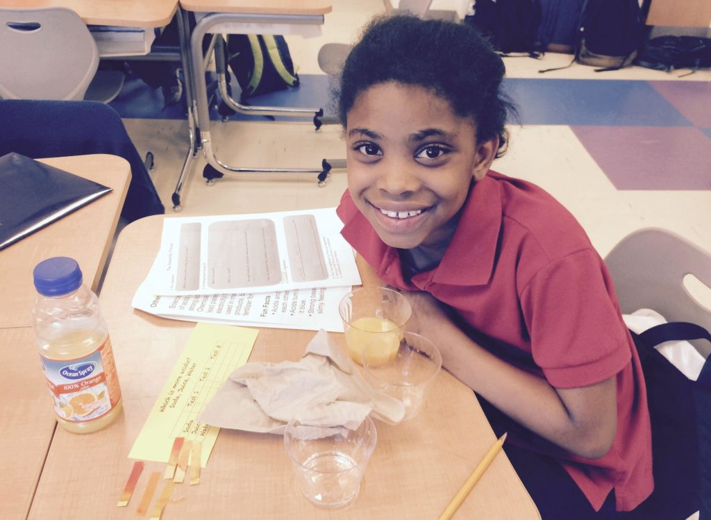 A student tutee with the DC STEM program smiles in the midst of a lab experiment.
