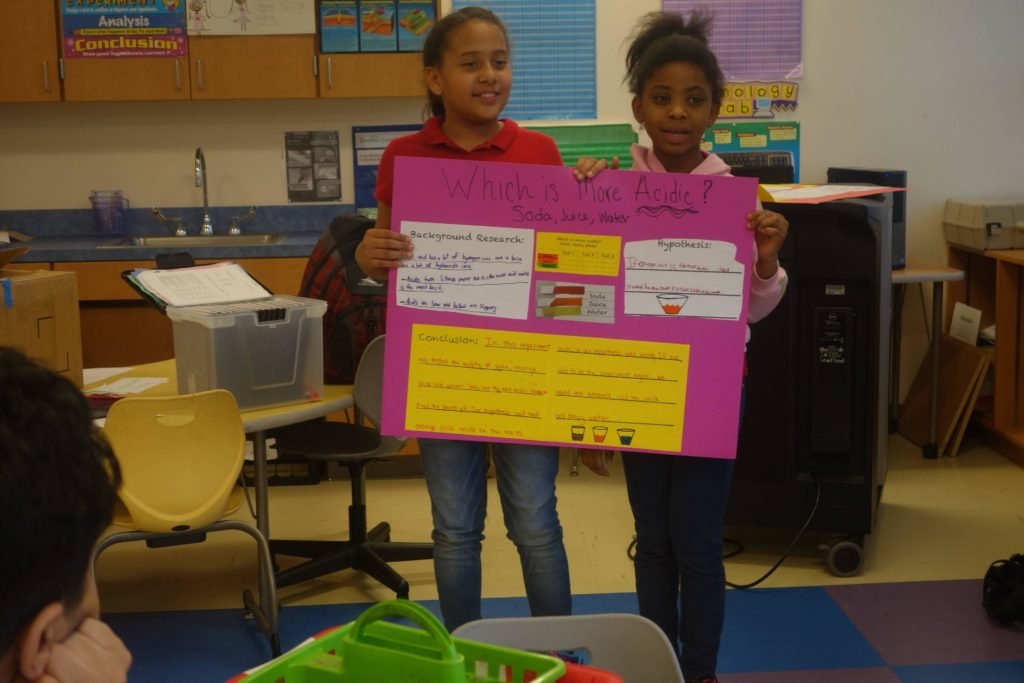 Two student tutees with the DC STEM program hold up a poster presentation they made.