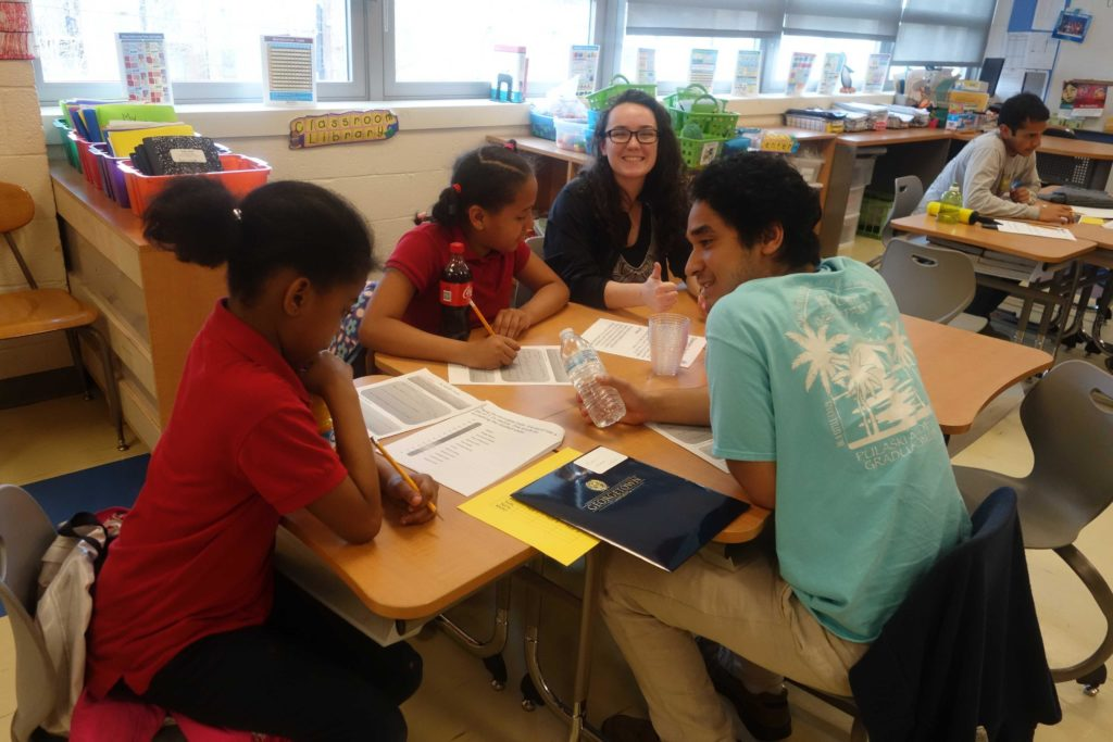 A Georgetown student and student tutees with the DC STEM program sit together at a table in the classroom working.