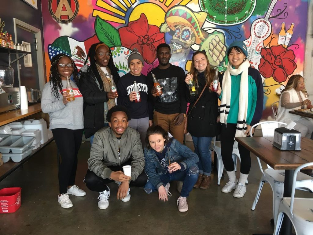 Georgetown students on an immersion trip gathered in front of a mural art wall.