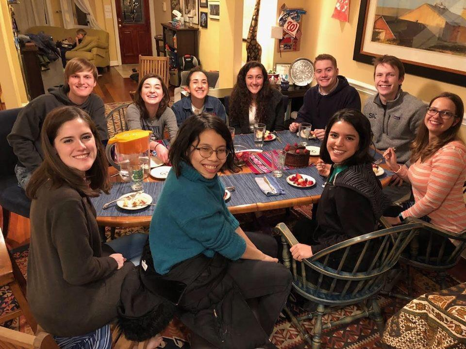 Georgetown students on an immersion trip sharing a meal together around a dining table.