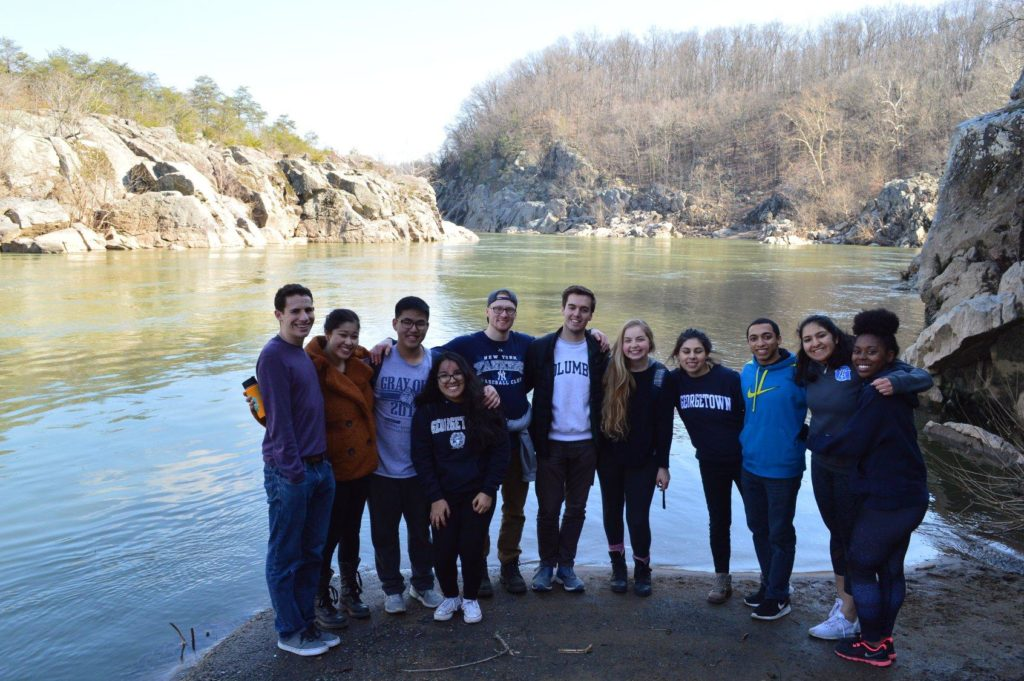 Georgetown students on an immersion trip gathered in front of a body of water.