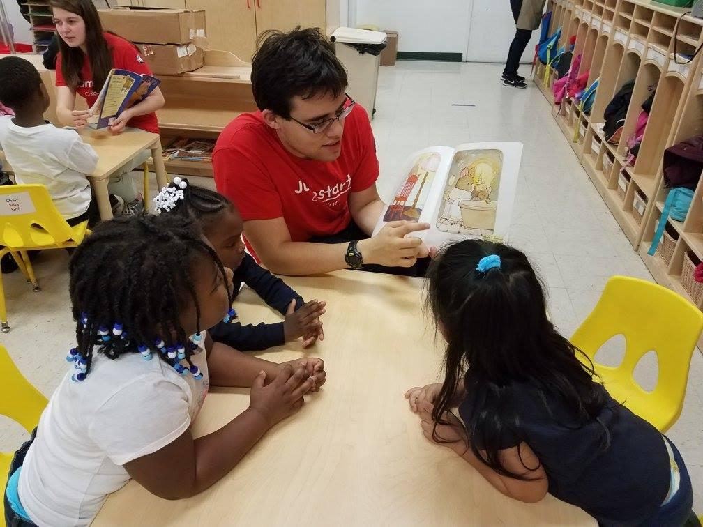 A Georgetown student tutor and three tutees with the Jumpstart program sit at a classroom table looking at a picture book.