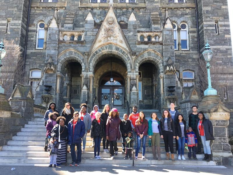 Georgetown members of the Jumpstart program stand together on the steps of Healy Hall on Georgetown's campus.