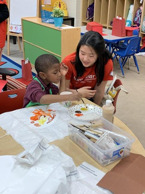 A Georgetown tutor and tutee with the Jumpstart program sit at a classroom table where the tutee paints.
