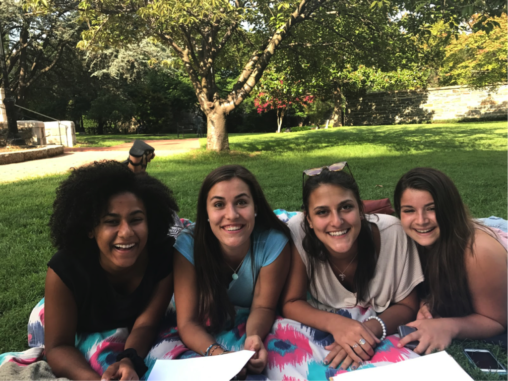Four FOCI participants lay on a picnic blanket shoulder-to-shoulder, smiling.