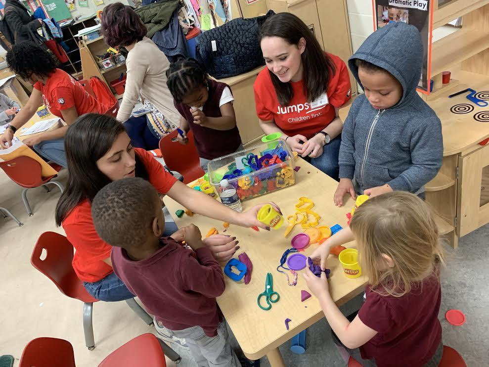 Georgetown student tutors and tutees in the Jumpstart program sit together at a classroom table playing with colored playdough.