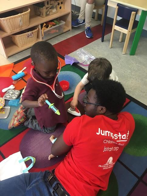 A Georgetown student tutor and two tutees with the Jumpstart program play with toy-doctor items on a rug in the classroom. The tutee is the play-doctor, while the tutor is the play-patient.