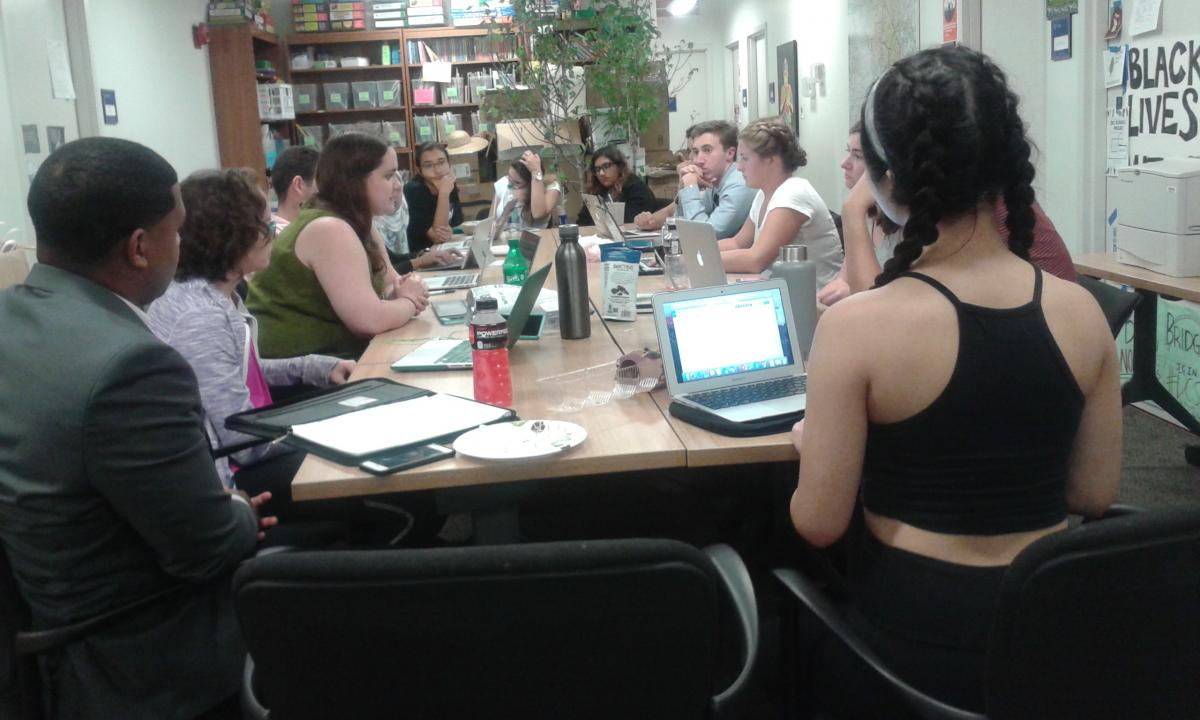 Students sit around a table