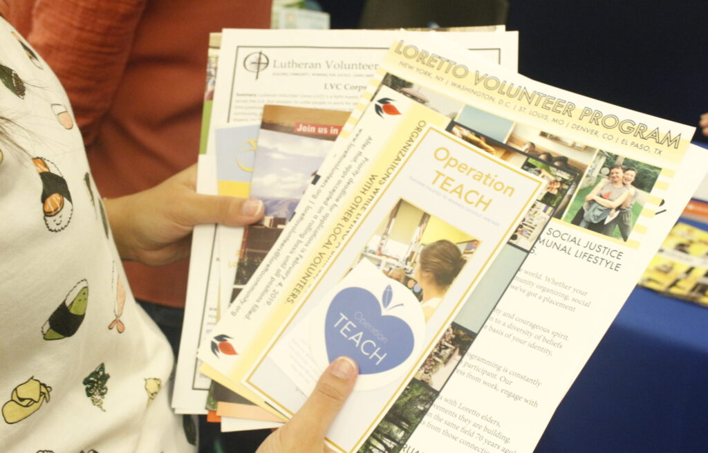 Student holding materials for various service organizations