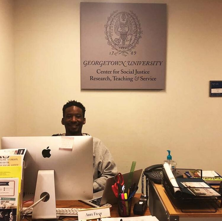 A Georgetown student who serves as a Center Operation Intern sits at the front desk in the CSJ.